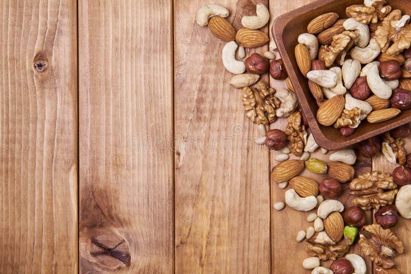 Φυσικό θρεπτικό μίγμα των διαφορετικών καρυδιών σε ένα τετραγωνικό ξύλινο πιάτο στον καφετή ξύλινο πίνακα στη δεξιά πλευρά Μίγμα  στοκ εικόνα με δικαίωμα ελεύθερης χρήσης