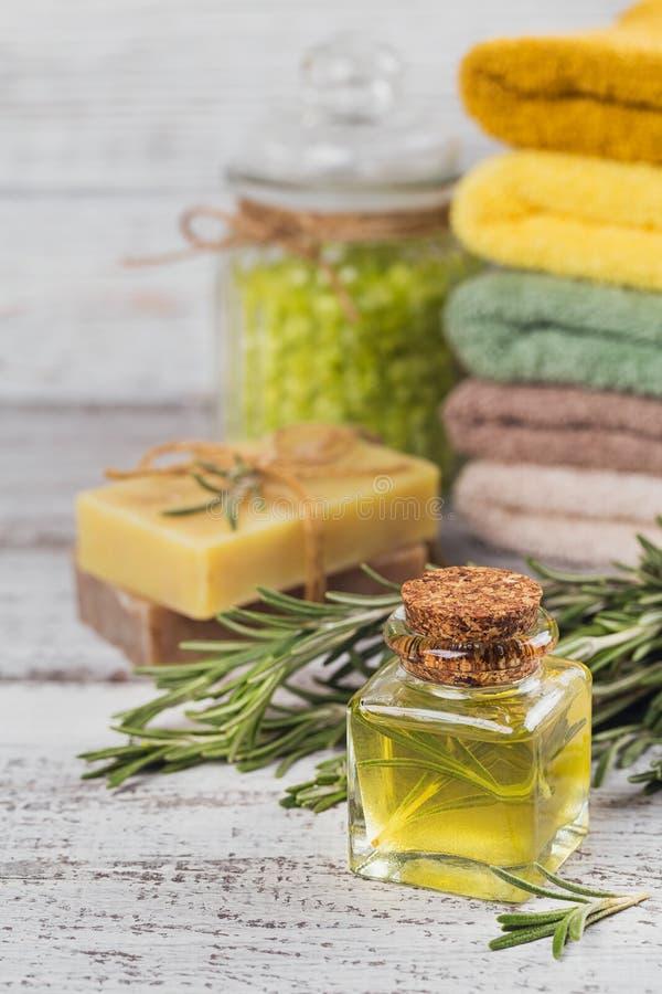 Φυσικό καλλυντικό πετρέλαιο και φυσικό χειροποίητο σαπούνι με το δεντρολίβανο επάνω στοκ φωτογραφία