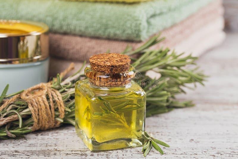 Φυσικό καλλυντικό πετρέλαιο και φυσικό χειροποίητο σαπούνι με το δεντρολίβανο επάνω στοκ εικόνα