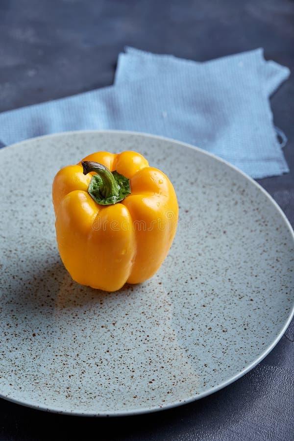 Φυσικό οργανικό κίτρινο πιπέρι κουδουνιών στο μαύρο πιάτο σε ένα μπλε υπόβαθρο Τοπ άποψη με τα διαστημικά, υγιή τρόφιμα αντιγράφω στοκ φωτογραφία με δικαίωμα ελεύθερης χρήσης