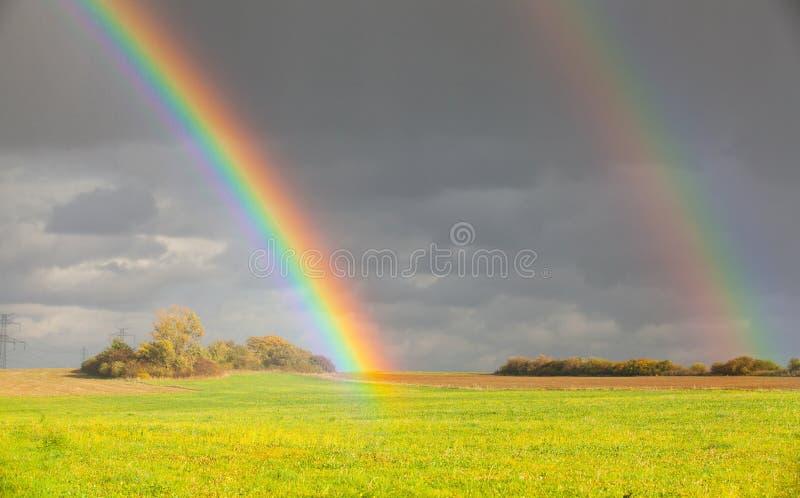 Φυσικό ουράνιο τόξο δύο πέρα από τον πράσινο τομέα μετά από τη βροχή στοκ φωτογραφία με δικαίωμα ελεύθερης χρήσης