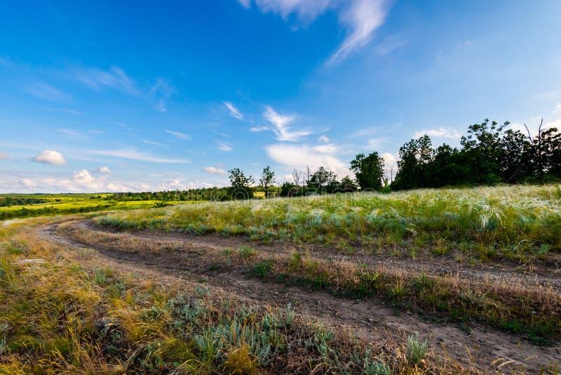 Φυσικό τοπίο επαρχίας με τον αγροτικό βρώμικο δρόμο στοκ εικόνες
