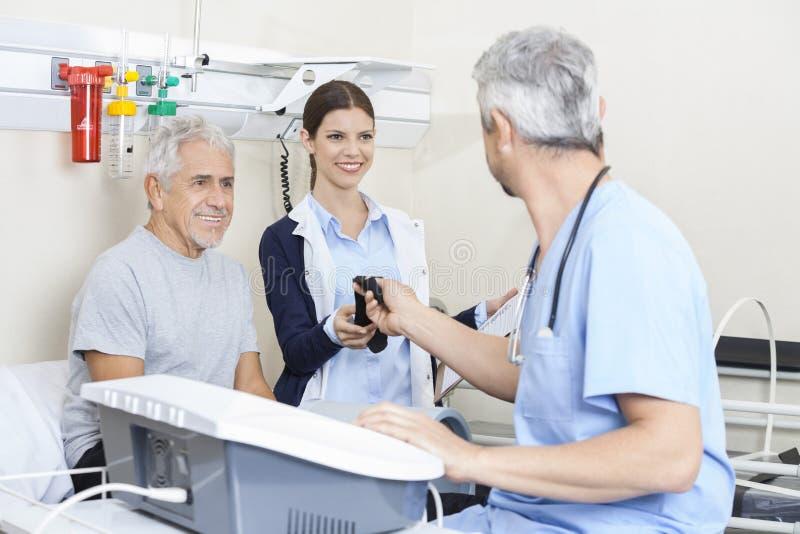 Φυσιοθεραπευτής που δίνει τη ζώνη στο συνάδελφο μεταχειριμένος το ανώτερο Μ στοκ φωτογραφία με δικαίωμα ελεύθερης χρήσης