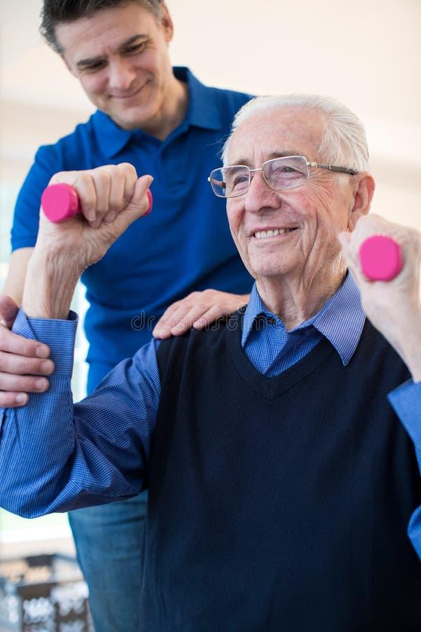 Φυσιοθεραπευτής που βοηθά το ανώτερο άτομο για να ανυψώσει τα βάρη χεριών στοκ φωτογραφία