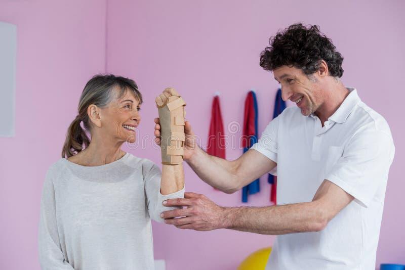 Φυσιοθεραπευτής που εξετάζει τον καρπό μιας ανώτερης γυναίκας στοκ εικόνες