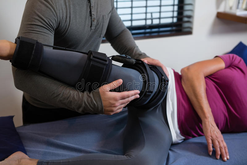 Φυσιοθεραπευτής που εξετάζει το γόνατο ασθενών του στοκ φωτογραφία