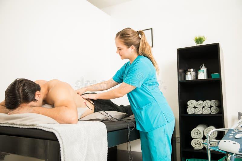 Φυσιοθεραπευτής που εφαρμόζει την ηλεκτρο υποκίνηση στην πλάτη του πελάτη στοκ φωτογραφία με δικαίωμα ελεύθερης χρήσης