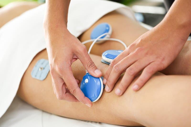 Φυσιοθεραπευτής που εφαρμόζει την ηλεκτρο υποκίνηση στη φυσική θεραπεία στοκ εικόνα