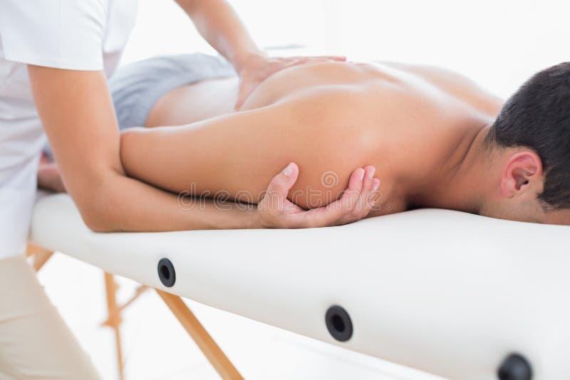 Φυσιοθεραπευτής που κάνει το μασάζ ώμων στον ασθενή της στοκ φωτογραφία με δικαίωμα ελεύθερης χρήσης