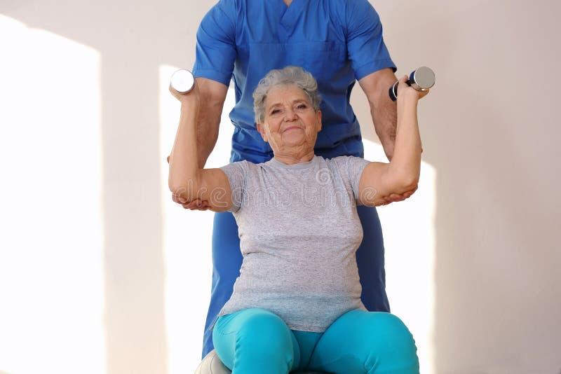 Φυσιοθεραπευτής που συνεργάζεται με τον ηλικιωμένο ασθενή στην κλινική στοκ εικόνα