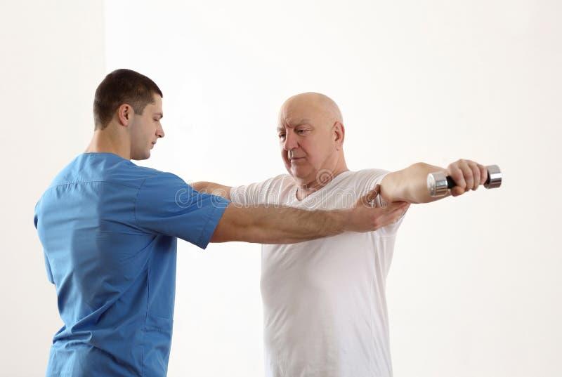Φυσιοθεραπευτής που συνεργάζεται με τον ηλικιωμένο ασθενή στην κλινική στοκ φωτογραφία με δικαίωμα ελεύθερης χρήσης