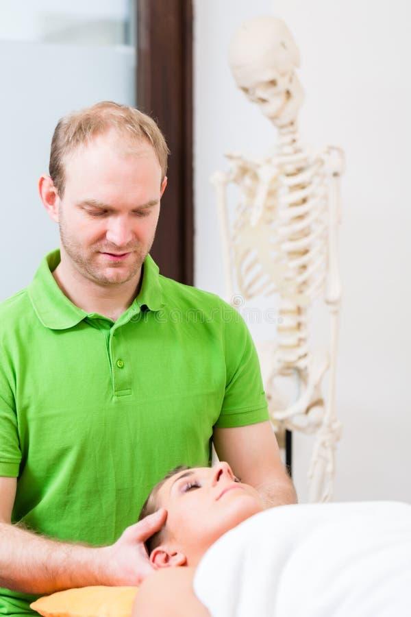 Φυσιοθεραπευτής που τρίβει το πρόσωπο της γυναίκας στοκ φωτογραφία