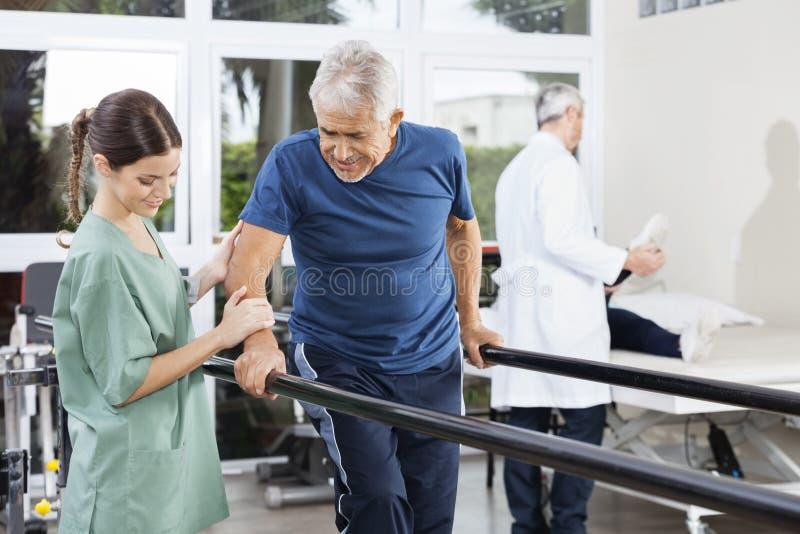 Φυσιοθεραπευτής που υπερασπίζεται το υπομονετικό περπάτημα μεταξύ του παράλληλου φραγμού στοκ εικόνες