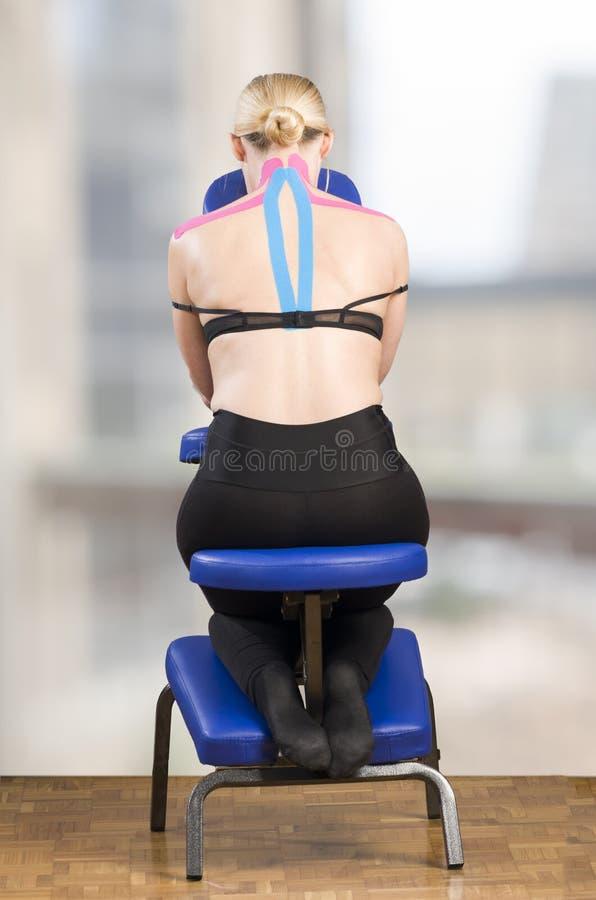 Φυσιοθεραπευτής, chiropractor που βάζει στη ρόδινη ταινία kinesio στο wo στοκ εικόνα με δικαίωμα ελεύθερης χρήσης