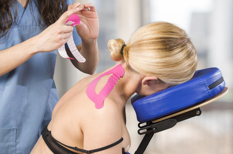 Φυσιοθεραπευτής, chiropractor που βάζει στη ρόδινη ταινία kinesio στο wo στοκ φωτογραφίες