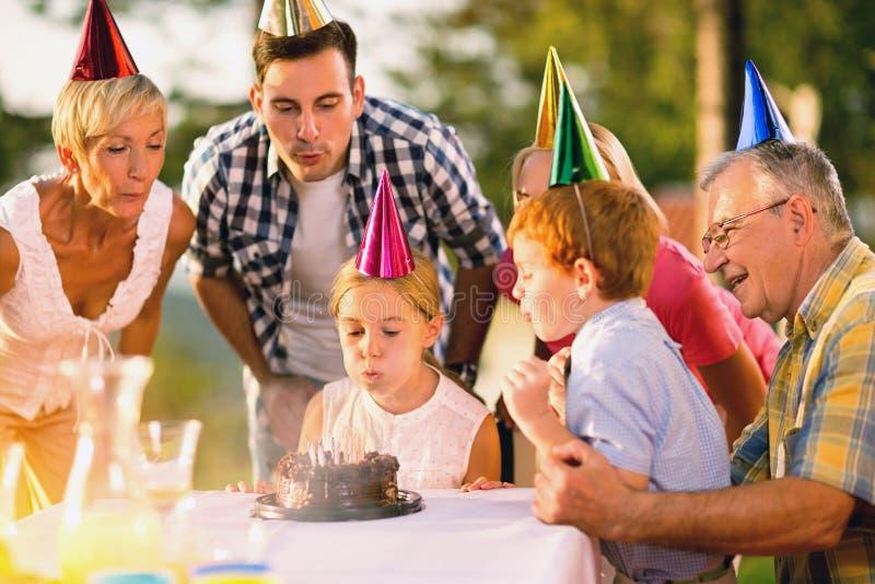 Φυσώντας κεριά κέικ κοριτσιών και οικογενειών γενεθλίων στοκ εικόνα με δικαίωμα ελεύθερης χρήσης