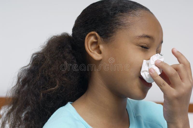 Φυσώντας μύτη κοριτσιών στοκ εικόνα