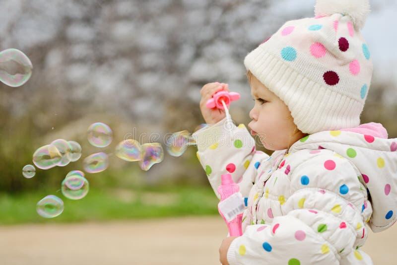 Φυσώντας φυσαλίδες σαπουνιών κοριτσιών μικρών παιδιών στοκ εικόνα με δικαίωμα ελεύθερης χρήσης