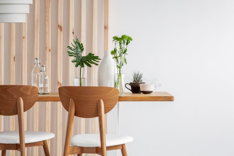 Φυτά σε μικρά βάζα σε μακριά ξύλινη τραπεζαρία σε φωτεινό εσωτερικό στοκ φωτογραφίες