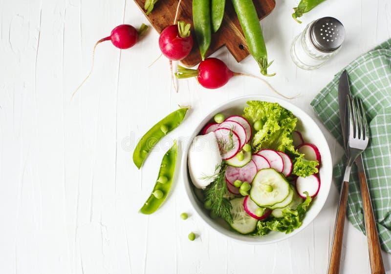 Φυτική σαλάτα άνοιξη με το ραδίκι, το αγγούρι και τα πράσινα μπιζέλια, τοπ άποψη, διάστημα αντιγράφων στοκ εικόνες με δικαίωμα ελεύθερης χρήσης