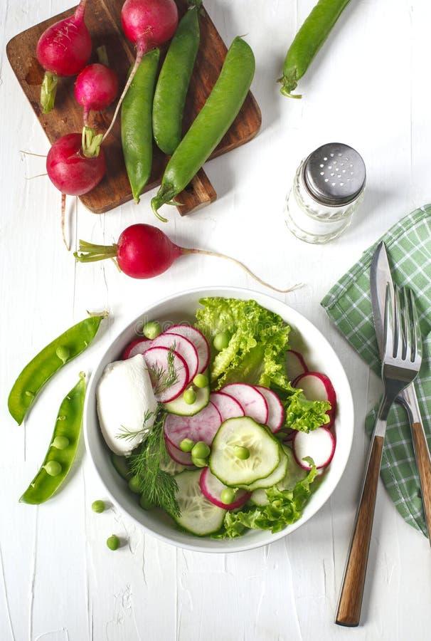 Φυτική σαλάτα άνοιξη με το ραδίκι, το αγγούρι και τα πράσινα μπιζέλια στοκ φωτογραφία