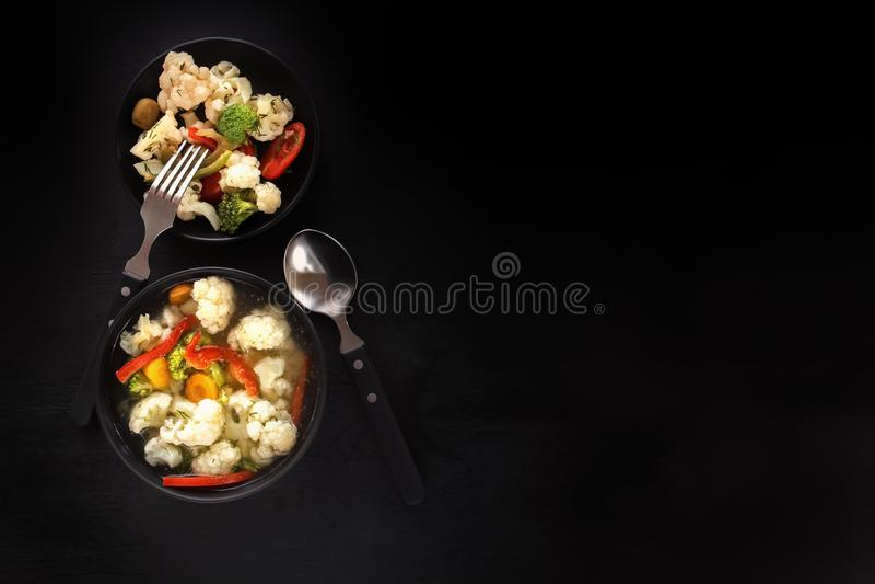 Φυτική σούπα και σαλάτα του κουνουπιδιού, των καρότων, της ντομάτας, του πιπεριού και των χορταριών σε ένα μαύρο πιάτο σε ένα μαύ στοκ εικόνες