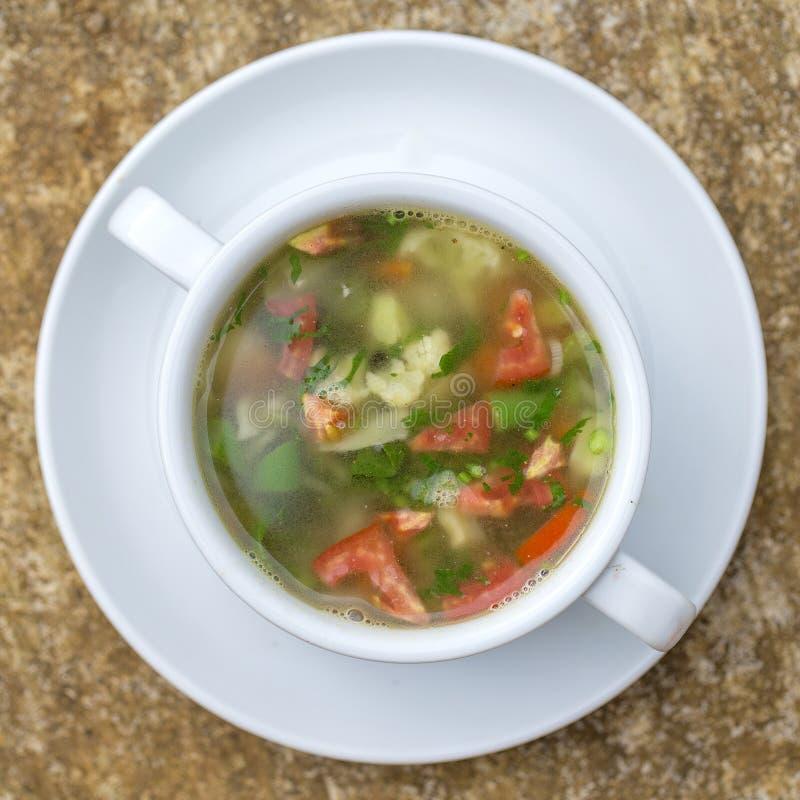 Φυτική σούπα με το κουνουπίδι συστατικών, κόκκινη ντομάτα, πράσινα φασόλια στο άσπρο πιάτο, τοπ άποψη στοκ εικόνα