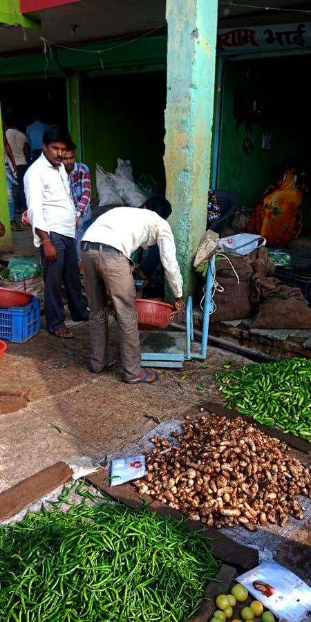 Φυτικός προμηθευτής που μετρά το βάρος αγαθών στην αγορά προϊόντων γεωργίας στοκ εικόνα