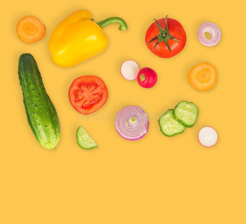 Φυτικό μίγμα στο κίτρινο απομονωμένο υπόβαθρο Φρέσκο κίτρινο πιπέρι, τεμαχισμένες ντομάτες, κρεμμύδι, στρογγυλή φέτα αγγουριών, κ στοκ φωτογραφίες