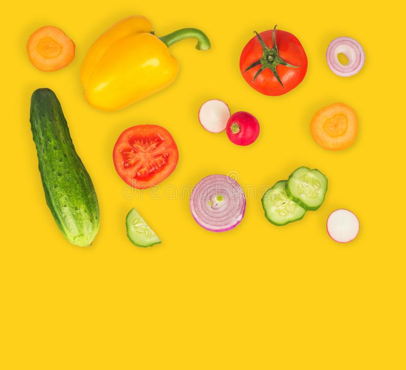 Φυτικό μίγμα στο κίτρινο απομονωμένο υπόβαθρο Φρέσκο κίτρινο πιπέρι, τεμαχισμένες ντομάτες, κρεμμύδι, στρογγυλή φέτα αγγουριών, κ στοκ εικόνα