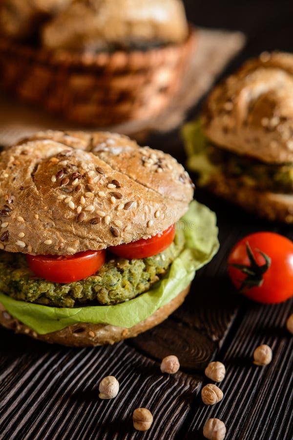 Φυτικό burger με chickpeas - fritter, μαρούλι και ντομάτα σπανακιού στοκ εικόνα