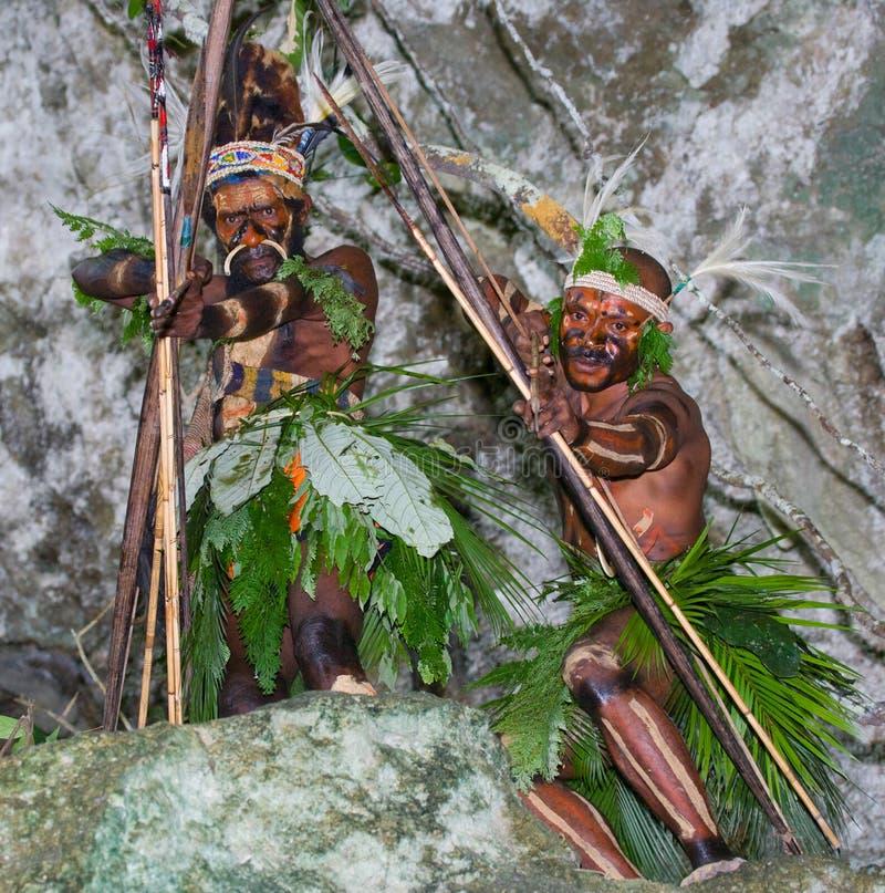 Φυλή Yaffi πολεμιστών στο πολεμικό χρώμα με τα τόξα και τα βέλη στη σπηλιά Νησί της Νέας Γουϊνέας στοκ εικόνες
