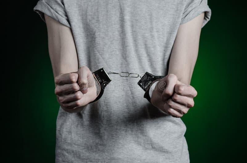 Φυλακή και καταδικασμένο θέμα: το άτομο με τις χειροπέδες σε δικοί του παραδίδει μια γκρίζα μπλούζα και το τζιν παντελόνι σε ένα  στοκ εικόνα