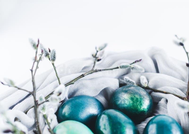 Φωλιά του υφάσματος με τα αυγά Πάσχας στο τυρκουάζ και το χρυσό που διακοσμούνται με την ιτιά γατών στο λευκό στοκ φωτογραφίες με δικαίωμα ελεύθερης χρήσης
