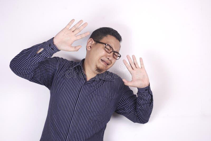 Φωνάζοντας λυπημένος νεαρός άνδρας που παρουσιάζει χειρονομία παράδοσης στοκ φωτογραφία