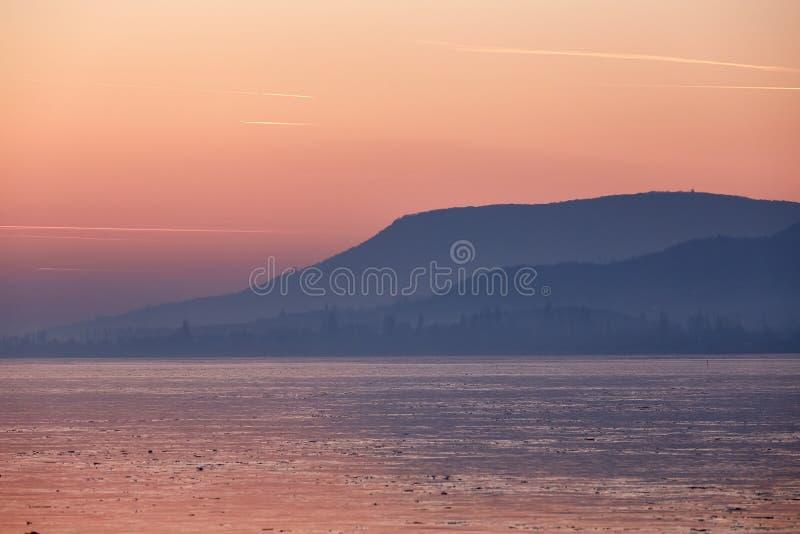 Φως ηλιοβασιλέματος πέρα από την παγωμένη λίμνη Balaton στην Ουγγαρία στοκ φωτογραφίες
