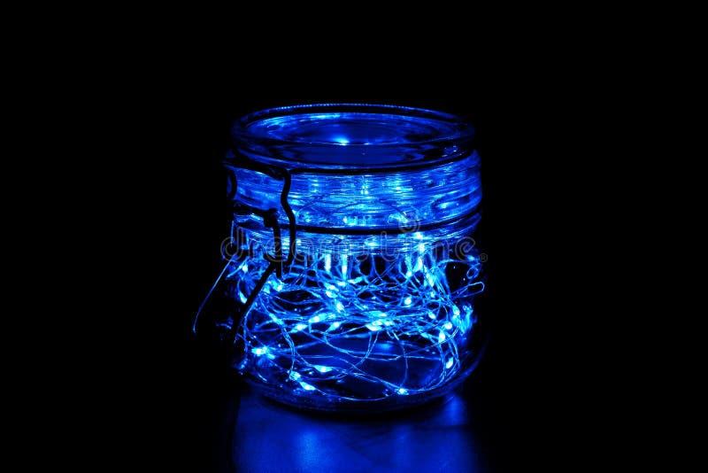 Φως νεράιδων σε ένα βάζο γυαλιού με το καπάκι, που απομονώνεται στο μαύρο υπόβαθρο στοκ εικόνες