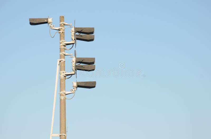 Φως σηματοφόρων τραίνων με έξι λαμπτήρες σε έναν υψηλό γκρίζο συγκεκριμένο στυλοβάτη ενάντια στο μπλε ουρανό στοκ εικόνα