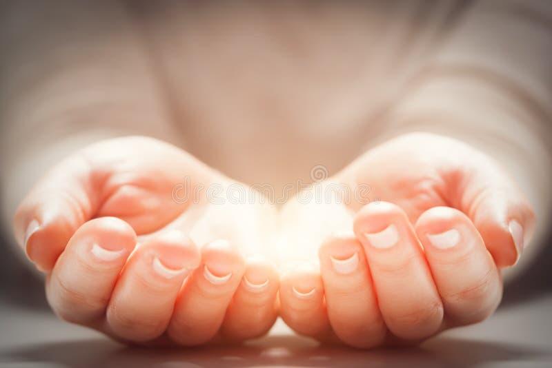 Φως στα χέρια της γυναίκας Έννοιες της διανομής, δίνοντας, νέα ζωή στοκ φωτογραφία