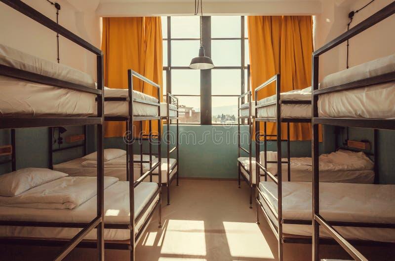 Φως στο παράθυρο της κρεβατοκάμαρας ξενώνων με τα καθαρά άσπρα κρεβάτια κουκετών για τους σπουδαστές και τους τουρίστες στοκ φωτογραφίες με δικαίωμα ελεύθερης χρήσης