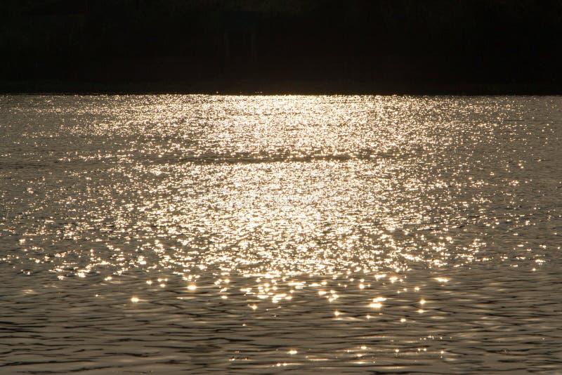 Φως του ήλιου από τα sunsets που απεικονίζονται στο νερό στοκ εικόνα