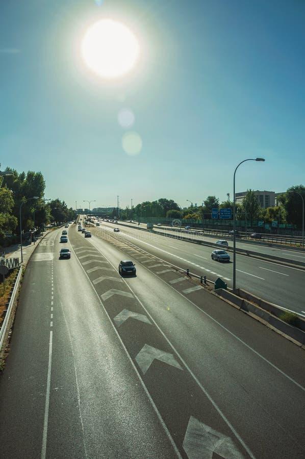 Φως του ήλιου πέρα από τα αυτοκίνητα σε μια εθνική οδό με την κυκλοφορία στη Μαδρίτη στοκ φωτογραφίες