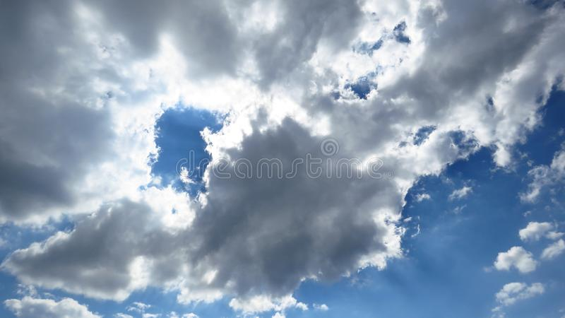Φως του ήλιου που έρχεται μέσω των άσπρων και γκρίζων σύννεφων θύελλας καθαρίσματος, μπλε ουρανός στοκ φωτογραφίες