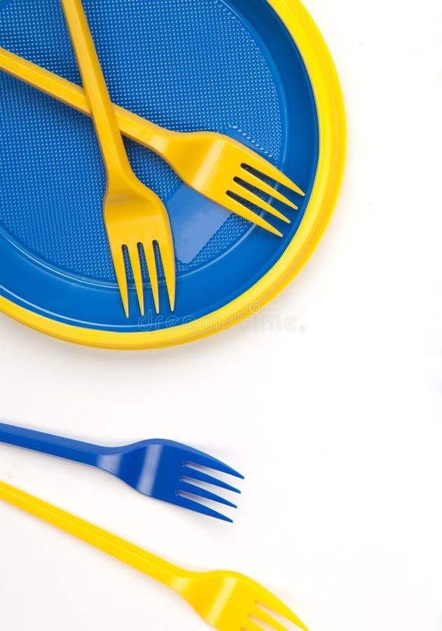 Φωτεινό μπλε και κίτρινο πλαστικό μίας χρήσης επιτραπέζιο σκεύος στη λευκιά ΤΣΕ στοκ φωτογραφίες με δικαίωμα ελεύθερης χρήσης