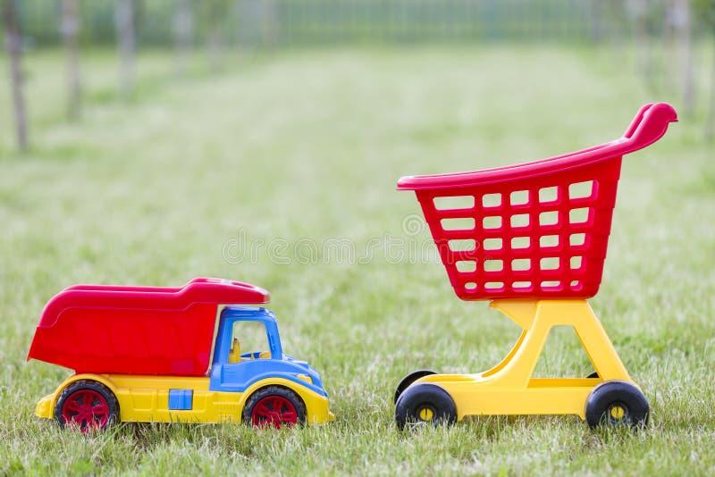Φωτεινά πλαστικά ζωηρόχρωμα παιχνίδια για τα παιδιά υπαίθρια την ηλιόλουστη θερινή ημέρα Φορτηγό αυτοκινήτων και χειράμαξα αγορών στοκ φωτογραφία με δικαίωμα ελεύθερης χρήσης