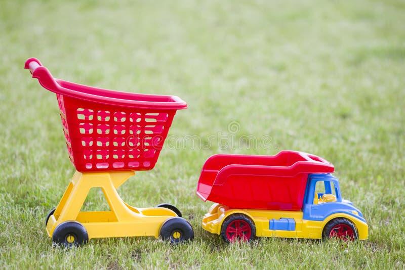 Φωτεινά πλαστικά ζωηρόχρωμα παιχνίδια για τα παιδιά υπαίθρια την ηλιόλουστη θερινή ημέρα Φορτηγό αυτοκινήτων και χειράμαξα αγορών στοκ φωτογραφίες με δικαίωμα ελεύθερης χρήσης