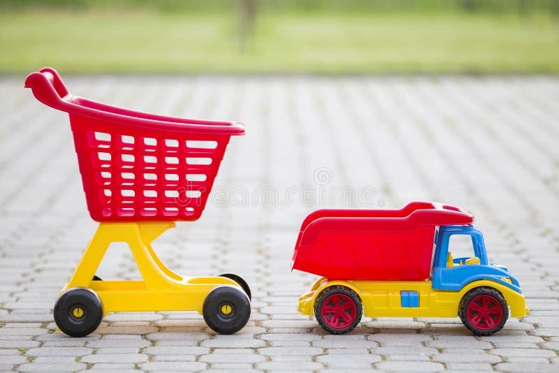 Φωτεινά πλαστικά ζωηρόχρωμα παιχνίδια για τα παιδιά υπαίθρια την ηλιόλουστη θερινή ημέρα Φορτηγό αυτοκινήτων και χειράμαξα αγορών στοκ εικόνα με δικαίωμα ελεύθερης χρήσης