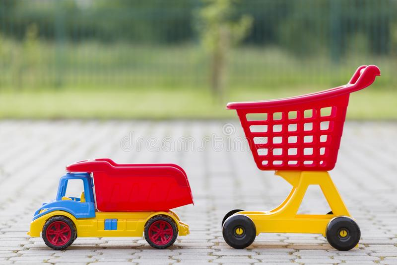 Φωτεινά πλαστικά ζωηρόχρωμα παιχνίδια για τα παιδιά υπαίθρια την ηλιόλουστη θερινή ημέρα Φορτηγό αυτοκινήτων και χειράμαξα αγορών στοκ εικόνα