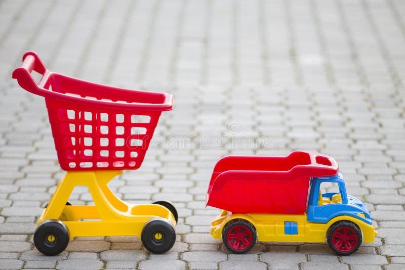Φωτεινά πλαστικά ζωηρόχρωμα παιχνίδια για τα παιδιά υπαίθρια την ηλιόλουστη θερινή ημέρα Φορτηγό αυτοκινήτων και χειράμαξα αγορών στοκ εικόνες