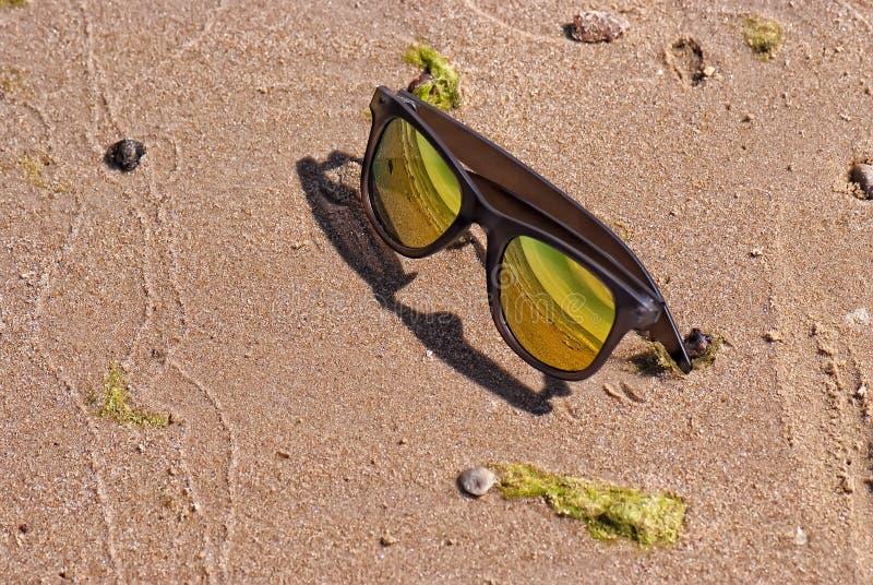 Φωτεινά χρυσά γυαλιά ηλίου χρώματος στην άμμο στοκ εικόνες